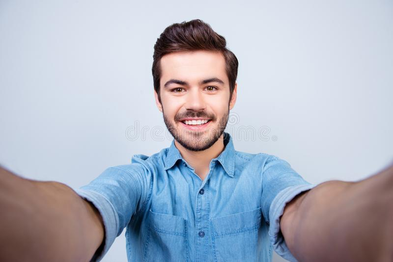 Handsome brunet young man is making selfie and smiling. He is we. Aring jeans shirt and behind him is a light blue background stock photo