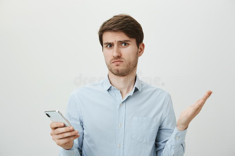 Handsome brunette guy with bristle shrugging and spreading hands with lifted eyebrows, expressing that he has no clue. What is going on, standing over gray royalty free stock photography