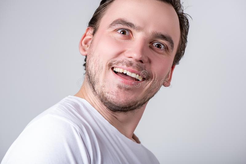 Handsome guy with bristles in a white T-shirt makes funny grimaces on his face stock photography