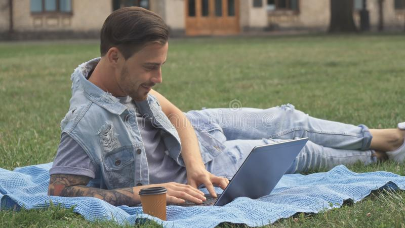 Guy lies on the lawn on campus. Handsome brunette guy lying on the green lawn on campus. Attractive young man using his laptop on the rug. Cute tattooed guy stock image
