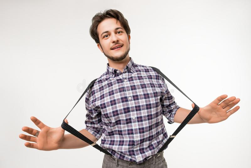Handsome brunette in plaid shirt view. Handsome brunette in plaid shirt and trousers with suspenders against white background isolated portrait stock images
