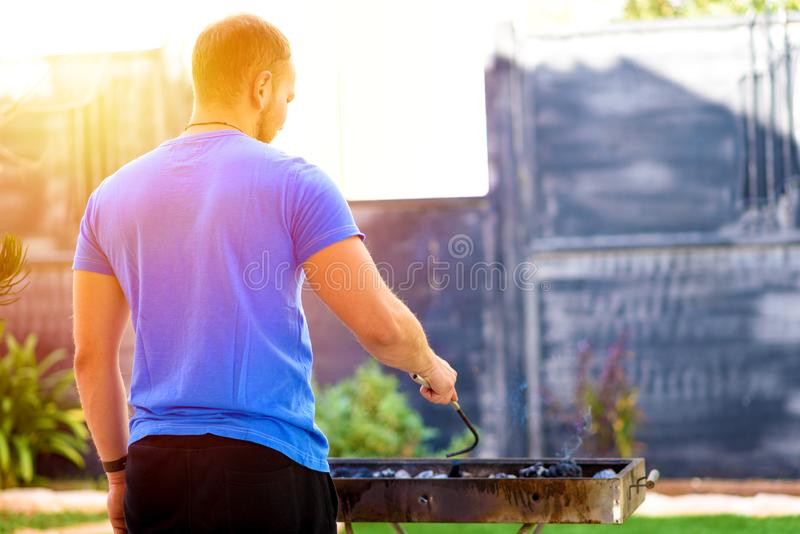 Handsome brutal bearded man cooking barbecue outdoors. stock image