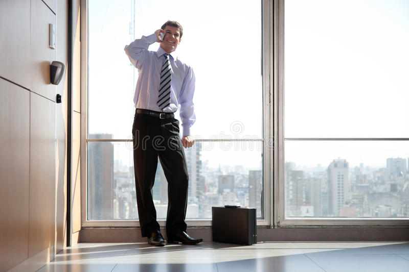 Handsome Business Man On Call. Full length of handsome young businessman talking on cell phone stock image