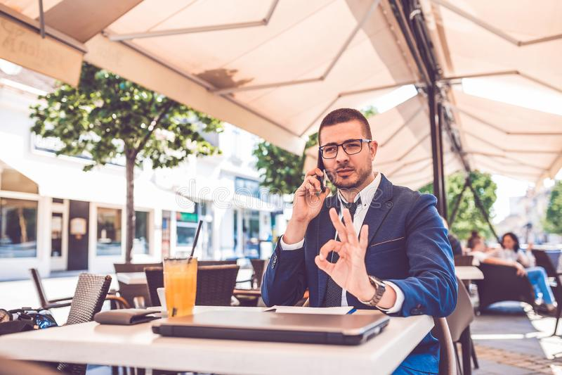 Handsome business man in glasses talking by mobile phone showing okay gesture during coffee break stock image