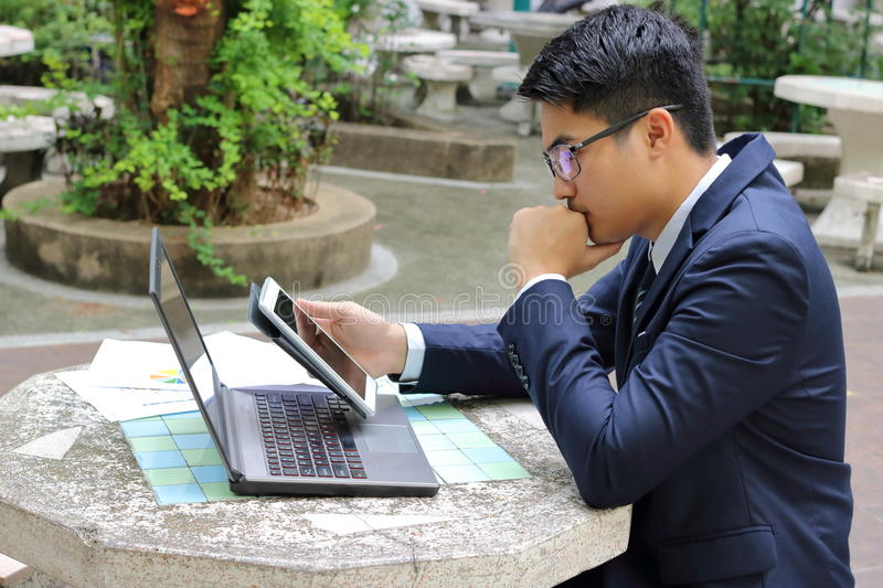Handsome business man holding his tablet for his work in the park royalty free stock images