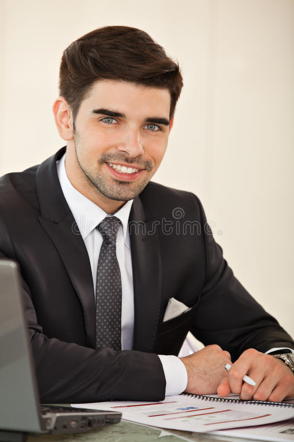 Handsome business man with laptop. Young handsome business man smiling sitting at his desk with a pen and a laptop stock images