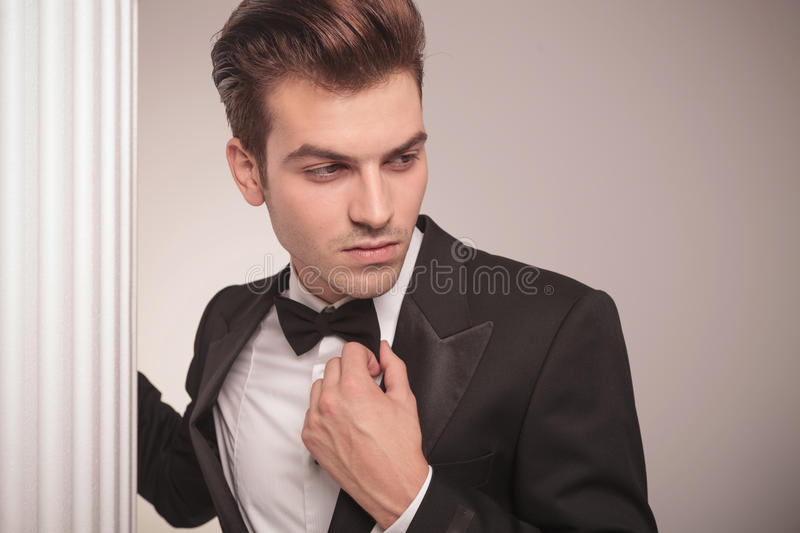 Handsome business man looking away. Close up picture of a young handsome business man looking away while fixing his bowtie royalty free stock photos