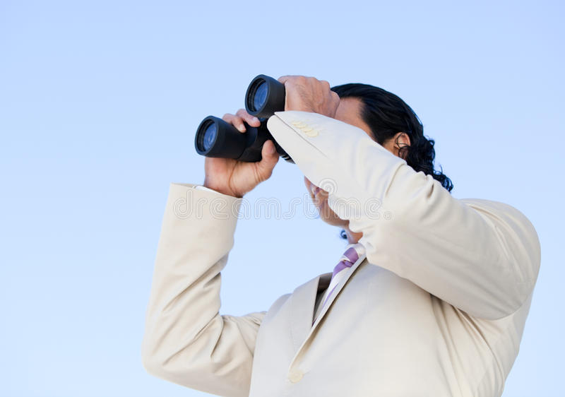 Handsome business man looking through binoculars. Portrait of an handsome business man looking through binoculars against a blue sky background stock photo