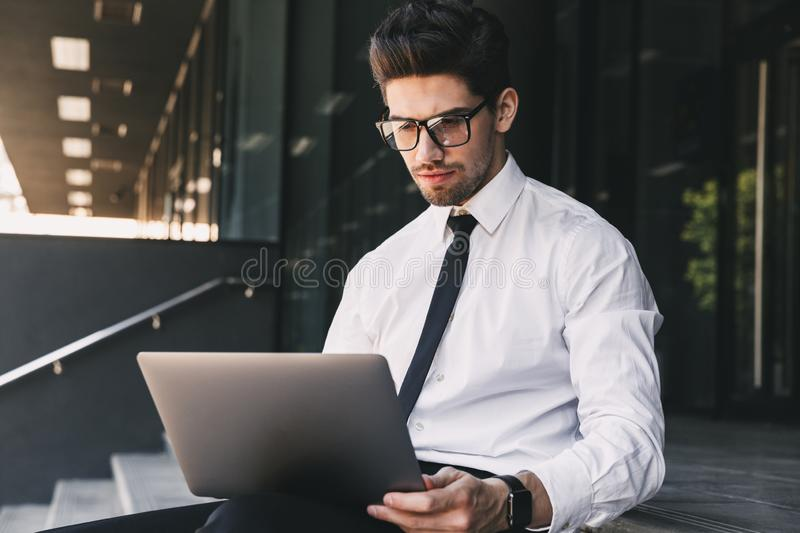 Handsome business man near business center using laptop computer. Image of handsome business man near business center using laptop computer stock photo