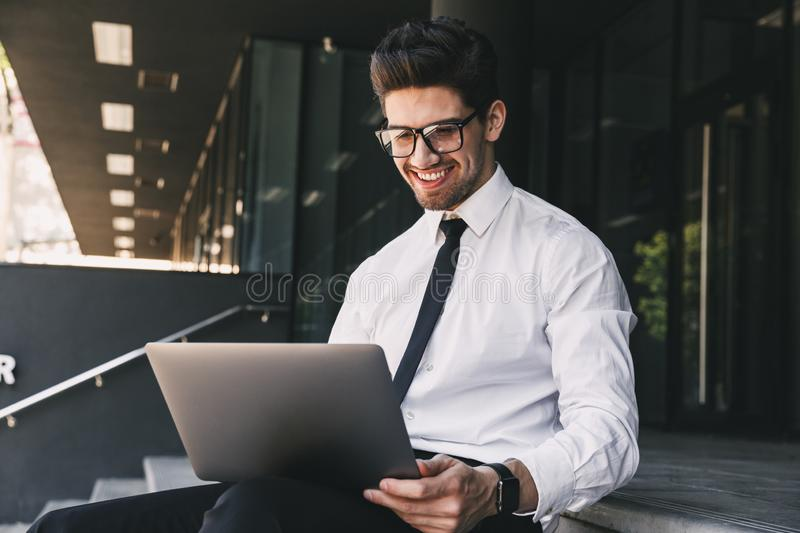 Handsome business man near business center using laptop computer. Image of handsome business man near business center using laptop computer royalty free stock photography