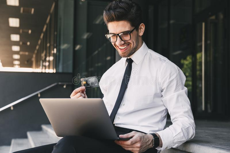 Handsome business man near business center using laptop computer. Image of handsome business man near business center using laptop computer holding credit card royalty free stock image