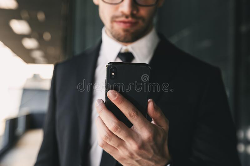Handsome business man near business center using mobile phone. Cropped image of handsome business man near business center using mobile phone stock image