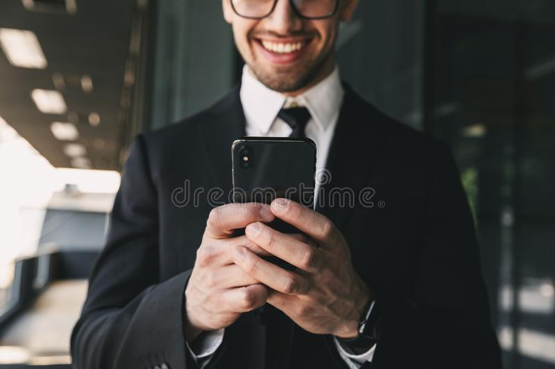 Handsome business man near business center using mobile phone. Cropped image of handsome business man near business center using mobile phone royalty free stock photography