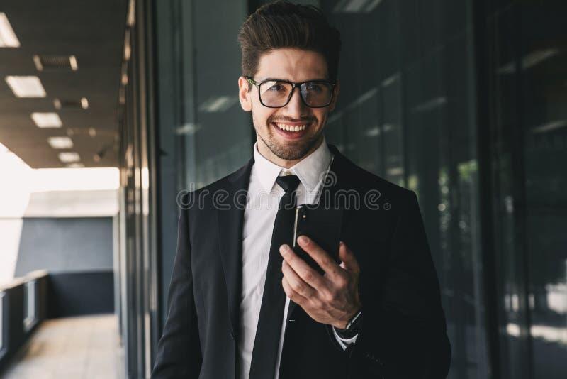 Handsome business man near business center using mobile phone. Image of handsome business man near business center using mobile phone royalty free stock photos