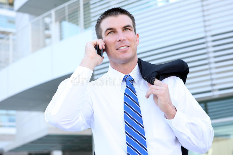 Handsome Business Man on Phone. A handsome business man on phone at the office building royalty free stock photos