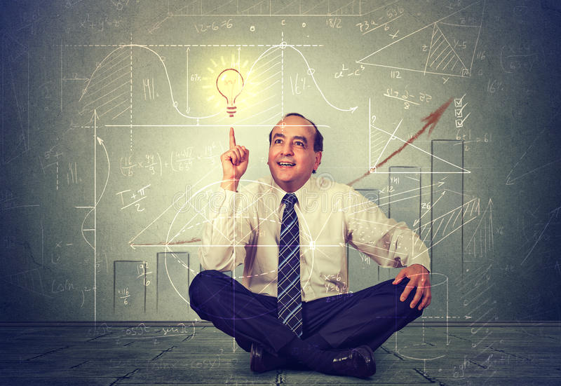 Handsome business man pointing at light bulb. Executive thinking over his strategy stock image