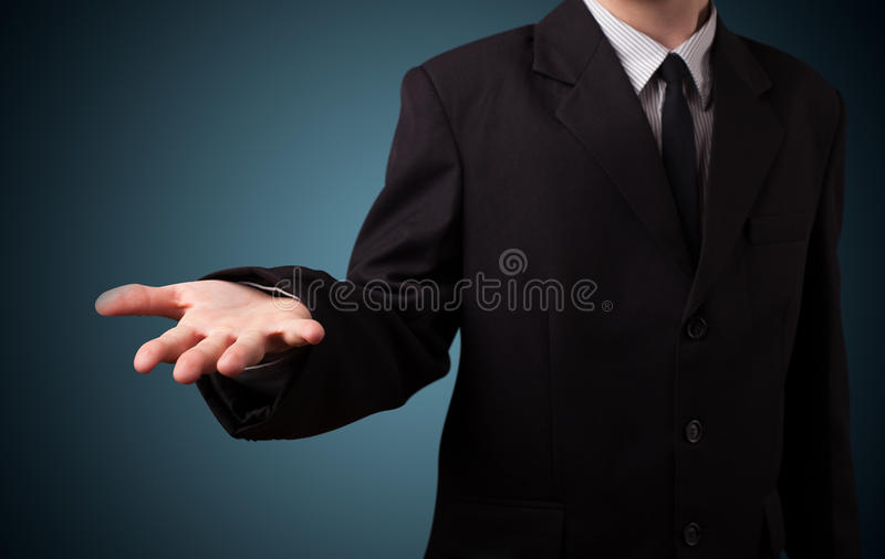 Handsome business man presenting with hand copy space stock image