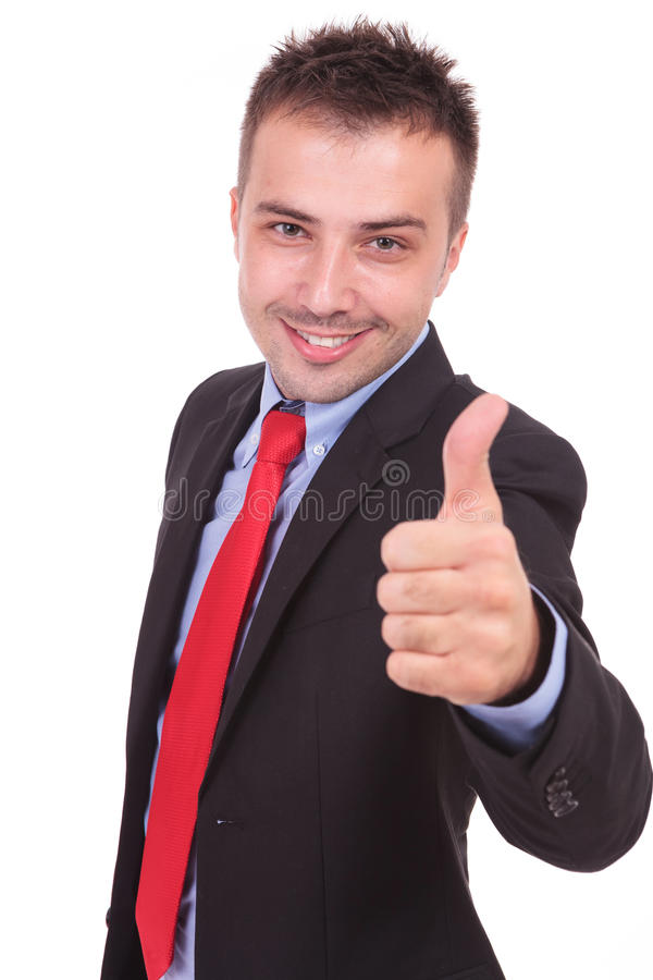 Handsome business man showing the thumbs up gesture. While smiling at the camera, isolated royalty free stock images