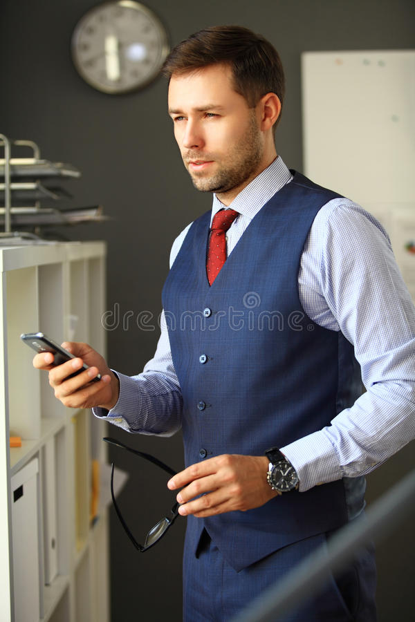 Handsome business man smiling at office. Handsome business man smiling at the office royalty free stock photos