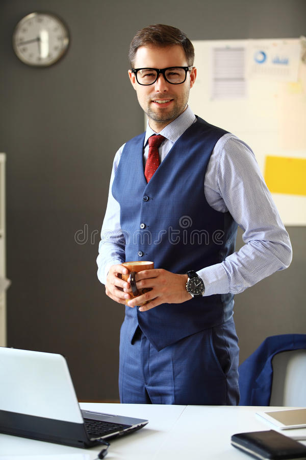 Handsome business man smiling at office. Handsome business man smiling at the office stock photos