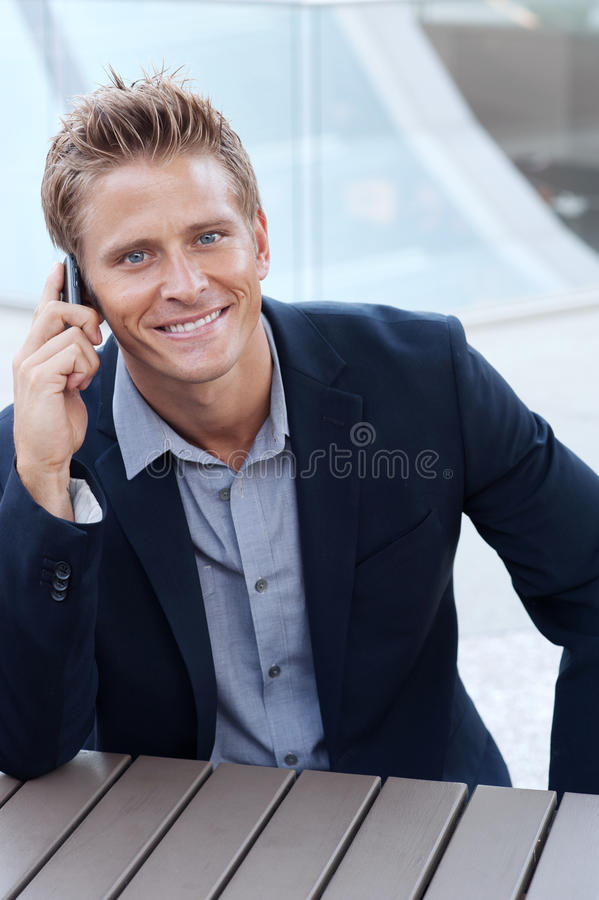 Handsome business man using cell phone, smil royalty free stock photography