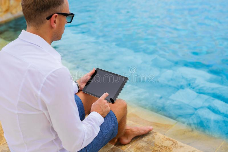 Business man using tablet by the pool stock images