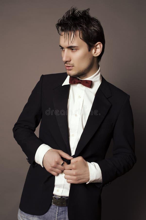 Handsome businesslike man with dark hair in elegant suit. Fashion studio photo of handsome businesslike man with dark hair in elegant suit royalty free stock photo