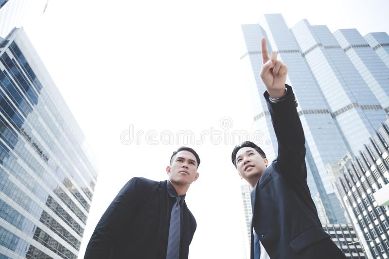 Handsome businessman is asking the way in the big city or metropolis and Attractive elder businessman is telling the way to go by royalty free stock images