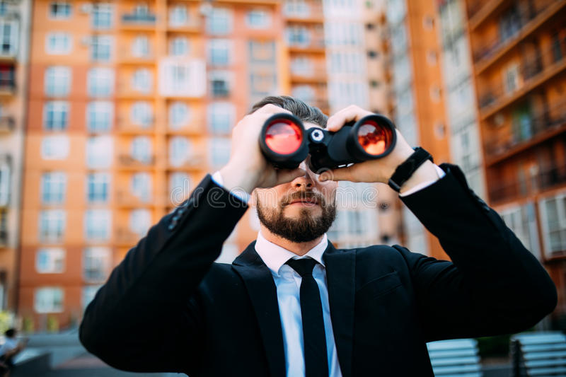 Handsome Businessman with binoculars spying on competitors outdoors royalty free stock photo