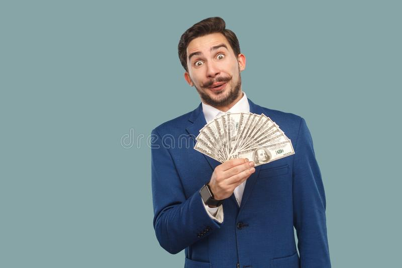 Handsome businessman in blue jacket standing and holding many do royalty free stock photography