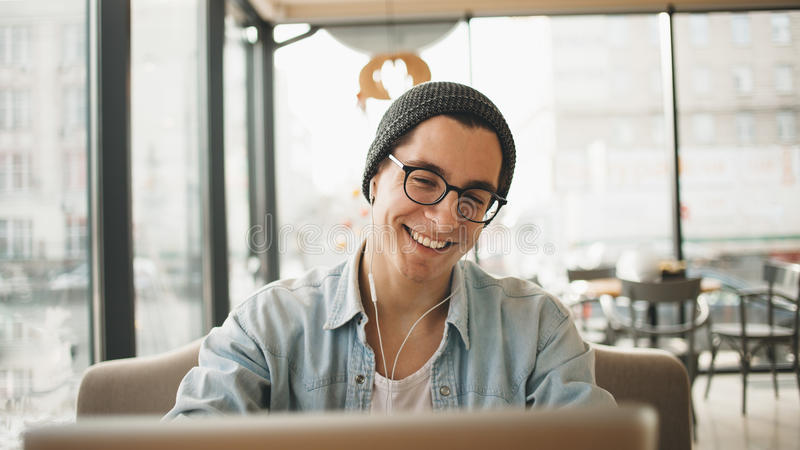Handsome businessman in casual wear and eyeglasses is using a laptop in cafe royalty free stock photography