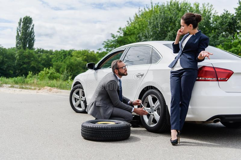 Handsome businessman changing tires on car on road businesswoman talking. By smartphone stock image