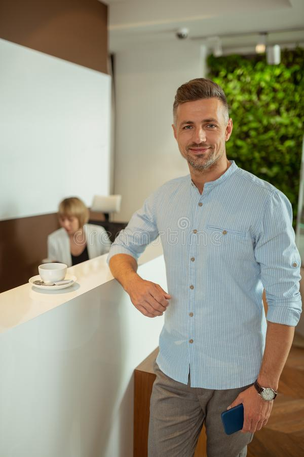 Handsome businessman drinking tea before going to the doctor royalty free stock photography