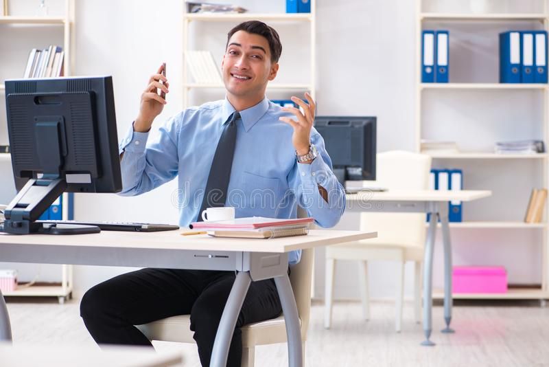The handsome businessman employee sitting at his desk in office. Handsome businessman employee sitting at his desk in office stock photo