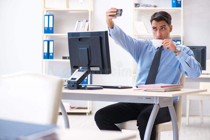 The handsome businessman employee sitting at his desk in office. Handsome businessman employee sitting at his desk in office royalty free stock photos