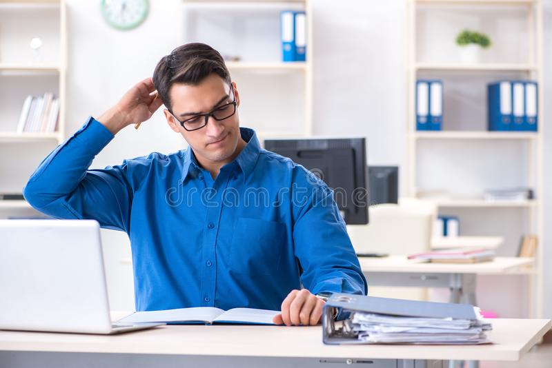 The handsome businessman employee sitting at his desk in office. Handsome businessman employee sitting at his desk in office royalty free stock images