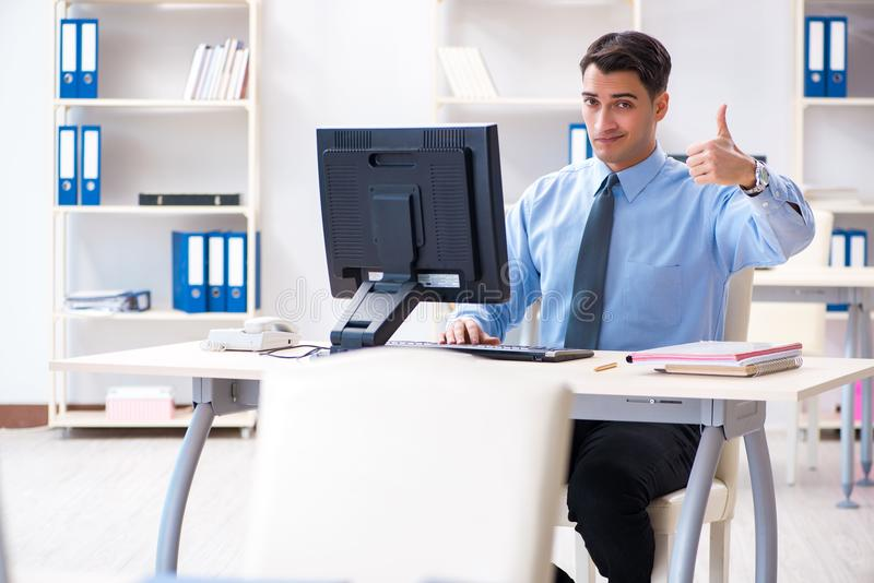 The handsome businessman employee sitting at his desk in office. Handsome businessman employee sitting at his desk in office stock images