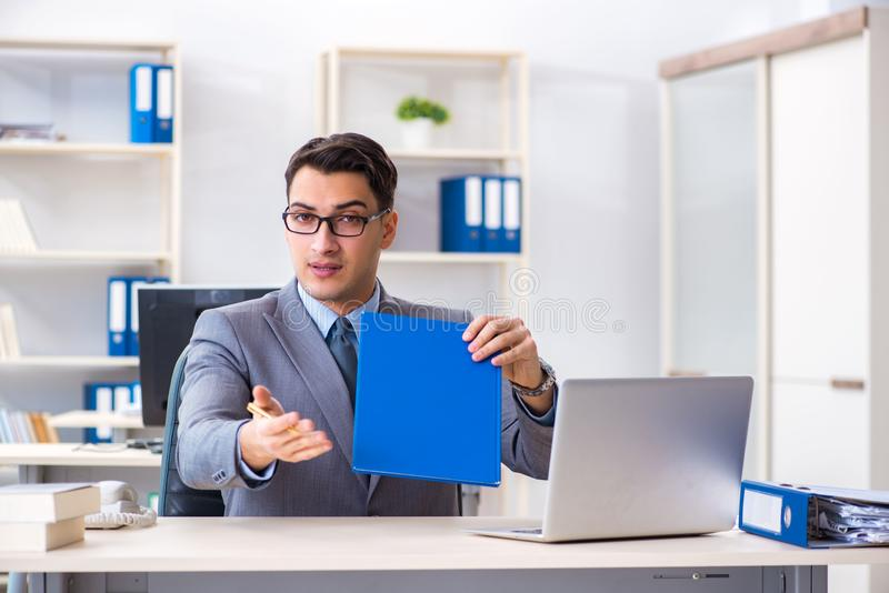 The handsome businessman employee sitting at his desk in office. Handsome businessman employee sitting at his desk in office royalty free stock image