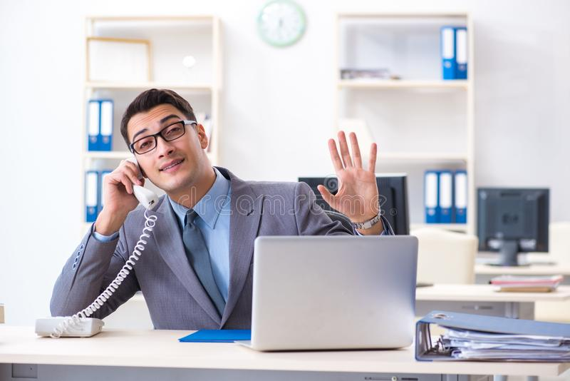 The handsome businessman employee sitting at his desk in office. Handsome businessman employee sitting at his desk in office stock photography