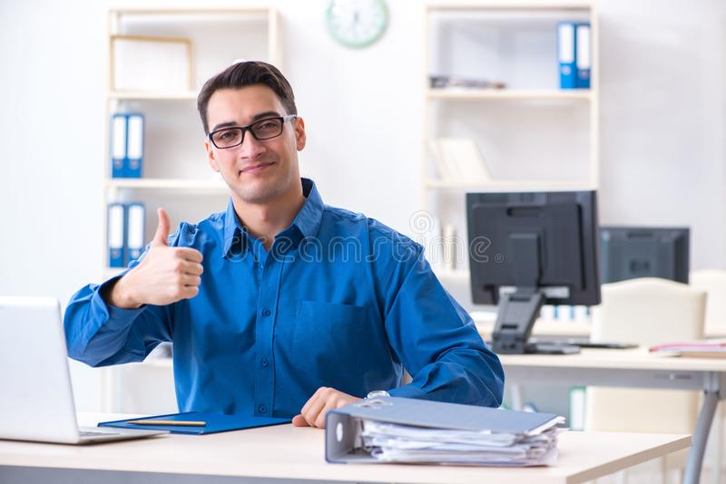 The handsome businessman employee sitting at his desk in office. Handsome businessman employee sitting at his desk in office stock image