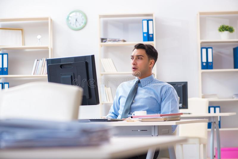 The handsome businessman employee sitting at his desk in office. Handsome businessman employee sitting at his desk in office royalty free stock photo
