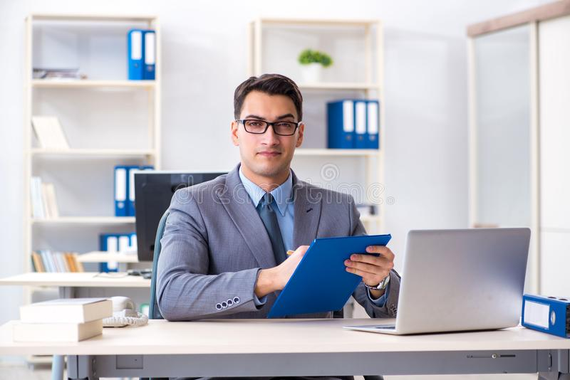 The handsome businessman employee sitting at his desk in office. Handsome businessman employee sitting at his desk in office royalty free stock photography