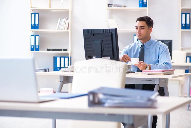 The handsome businessman employee sitting at his desk in office. Handsome businessman employee sitting at his desk in office stock photos