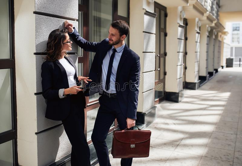 Handsome businessman explaining something to his beautiful female colleague royalty free stock image