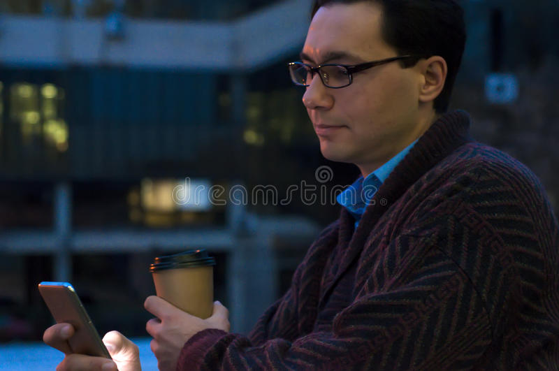 Handsome businessman in eyeglasses is using a smartphone, holding a cup of coffee and smiling while standing near the window. Handsome businessman in eyeglasses royalty free stock photo