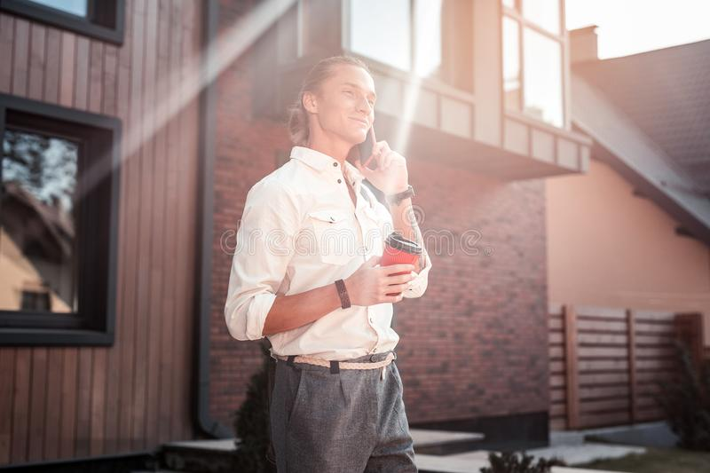 Handsome businessman feeling good in the morning holding takeaway coffee. Takeaway coffee. Handsome stylish businessman feeling really good in the morning royalty free stock photos