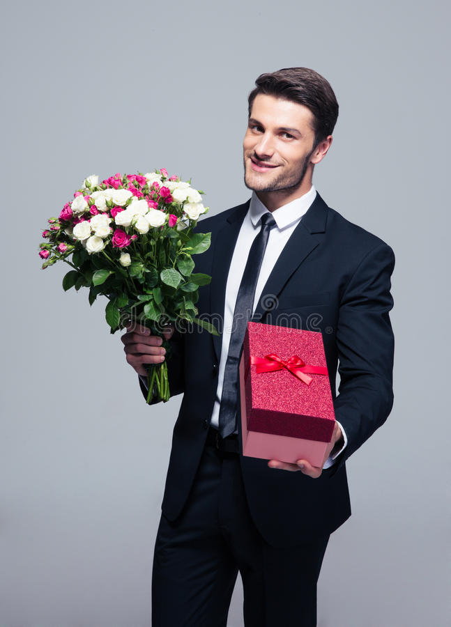 Handsome businessman with flowers and gift box. Standing over gray background stock photography