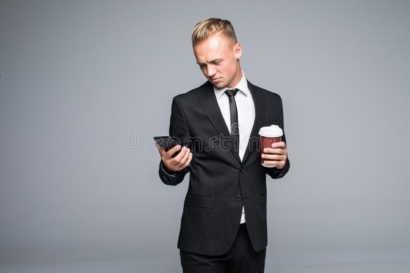 Handsome businessman in formal suit is using a smart phone, holding a cup of coffee on gray background stock image