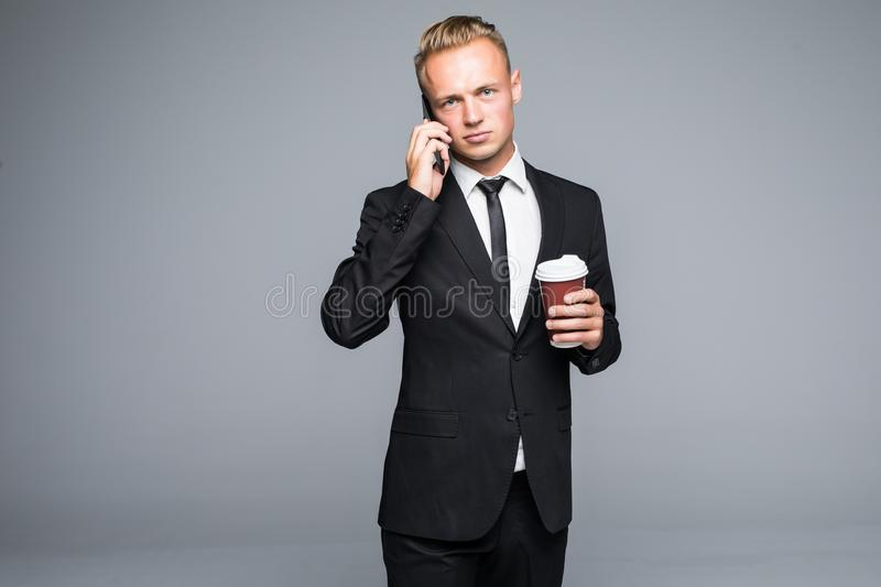 Handsome businessman in formal suit is using a smart phone, holding a cup of coffee on gray background stock photo