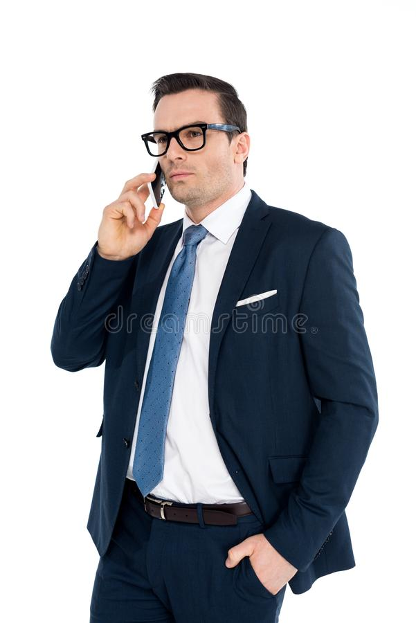 Handsome businessman in formal wear talking by smartphone and looking away. Isolated on white royalty free stock images